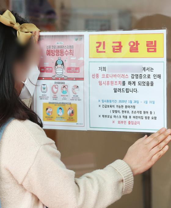 임시 휴원 안내문 붙이는 어린이집 관계자. [연합뉴스]