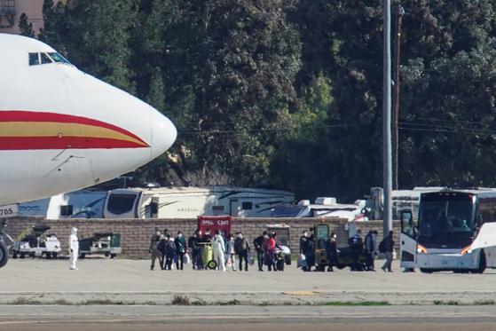 우한에 머물던 미국인 200여 명을 태운 국무부 전세기가 29일(현지시간) 오전 미국 캘리포니아주 리버사이드카운티의 마치 공군기지에 내렸다. 비행기에서 내린 승객들이 버스를 타기 위해 이동하고 있다. [로이터=연합뉴스]