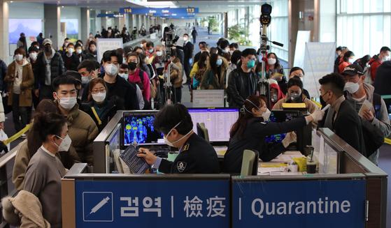 29일 중국 광저우에서 출발한 항공기 여객들이 인천국제공항 제1터미널을 통해 입국하며 발열 검사 및 검역 질의서를 제출받고 있다. 최정동 기자
