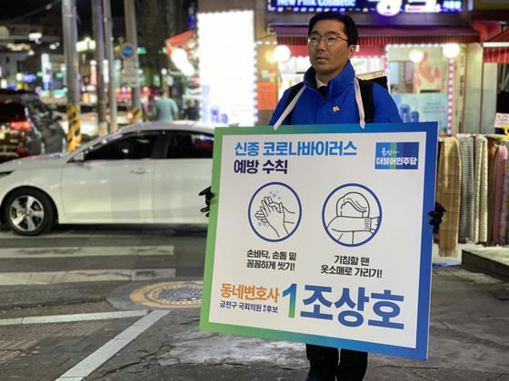 조상호 예비후보(서울 금천, 민주당)가 29일 저녁 8시 30분 시흥사거리 인근 횡단보도에서 신종코로나 예방 수칙이 담긴 팻말을 들고 선거 운동을 진행했다. 정희윤 기자