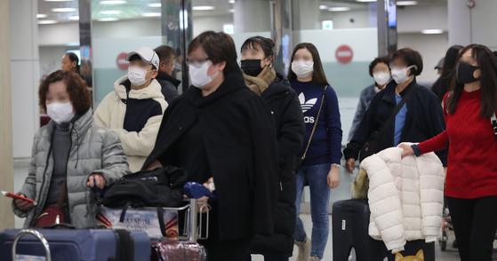 (제주=뉴스1) 오현지 기자 = 신종 코로나바이러스 감염증(우한폐렴)이 확산하는 가운데 29일 오후 제주국제공항에 도착한 여행객들이 마스크를 쓰고 입국장에 들어서고 있다.2020.1.29/뉴스1