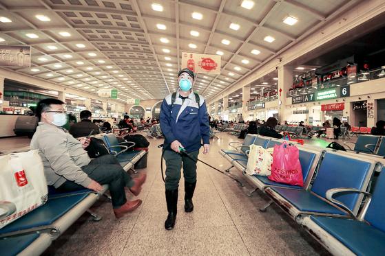 지난 22일 중국 후베이성 우한 한커우 기차역에서 방역 작업 중인 직원의 모습. [AFP=연합뉴스]