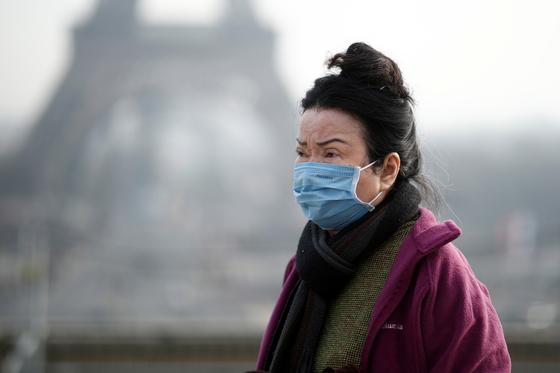 지난 25일 프랑스 파리에서 마스크를 쓴 관광객이 에펠탑 인근을 지나고 있다. [로이터=연합뉴스]