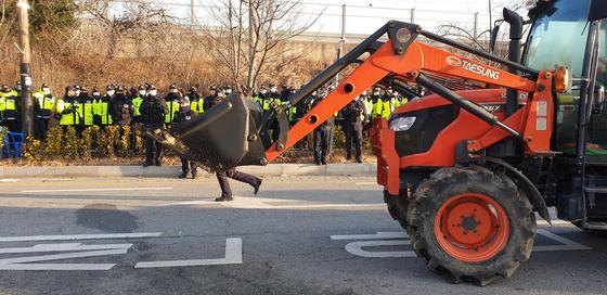 30일 오전 경찰이 충남 아산 경찰인재개발원 앞에 설치된 트랙터 등을 철거하고 있다. 이 장비는 전날 주민들이 설치했다. 주민들은 우한 교민을 이곳에 수용한다는 소식이 알려지자 중장비를 설치하고 거칠게 항의했다. 김방현 기자