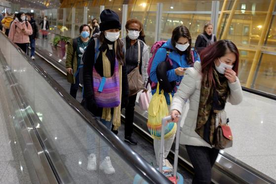 지난 25일 중국 베이징 공항에 도착한 여행객들이 마스크를 쓴 채 에스컬레이터를 타고 이동하고 있다. [연합뉴스]