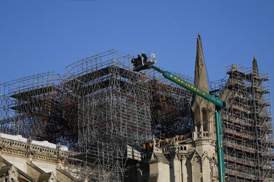1월 6일 프랑스 파리에서 인부들이 크레인을 타고 올라가 노트르담 대성당 지붕 복원공사를 위한 안정화 작업을 하고 있다. [AP=연합뉴스]