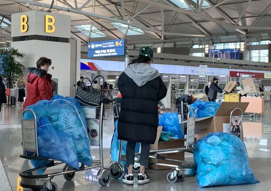 신종코로나바이러스감염증이 세계적으로 확산하고 있는 가운데 28일 오후 인천국제공항 출국장에서 중국여행자들이 한국에서 구입한 마스크를 비닐봉투에 가득담아 출국수속을 기다리고 있다. (독자제공) [뉴스1]
