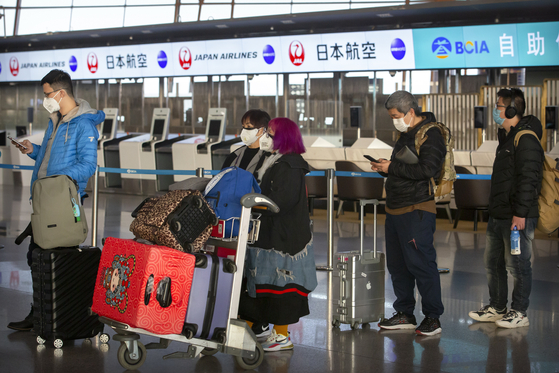지난달 30일 중국 베이징 공항에서 마스크를 쓴 관광객들이 줄을 서 있다. [AP=연합뉴스]