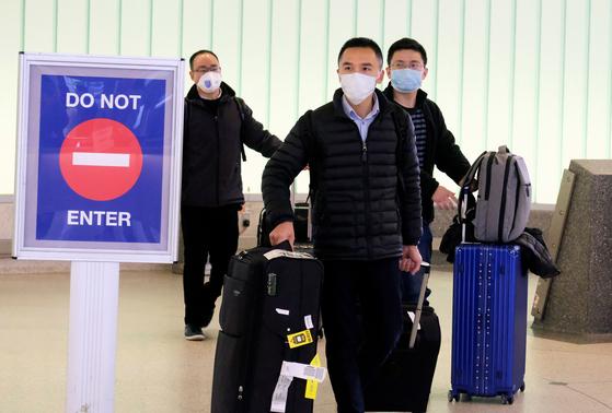 26일 미국 로스앤젤레스 국제공항에서 중국 상하이에서 출발한 승객들이 마스크를 쓰고 도착하고 있다. [로이터=연합뉴스]