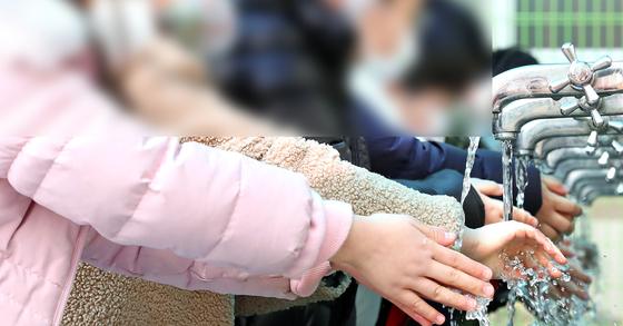 지난 1월 28일 개학한 대구의 한 초등학교에서 학생들이 점심시간을 맞아 수돗가에서 손을 씻고 있다. [뉴스1]