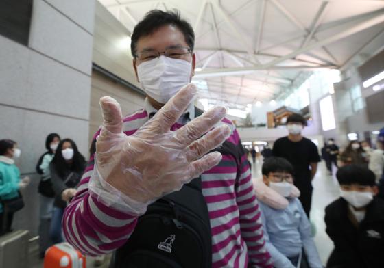 인천국제공항 1터미널에서 한 출국자가 출국심사대로 향하며 비닐장갑을 낀 손을 보여주고 있다. [연합뉴스]