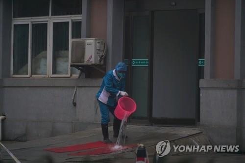중국 우한의 병원 입구에서 청소 중인 직원. [AP=연합뉴스]