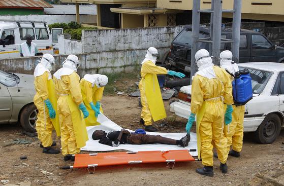 지난 2014년 에볼라가 발병했을 때 라이베리아에서 시신을 수습하고 있는 보건당국 요원들. [EPA=연합뉴스]