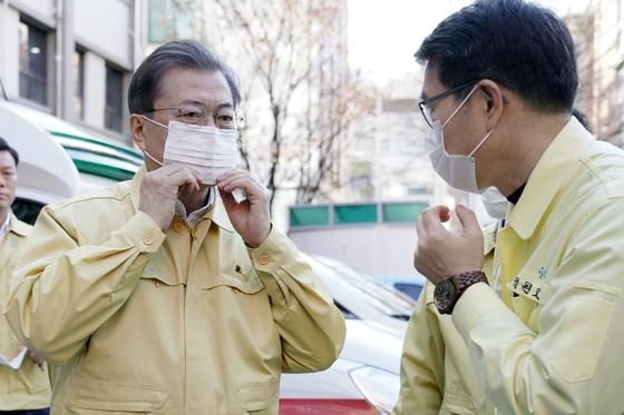 문재인 대통령(왼쪽)이 5일 오전 신종 코로나바이러스 감염증 대응 시설인 서울 성동구 보건소에 도착해 마스크를 착용하고 있다. [청와대사진기자단]