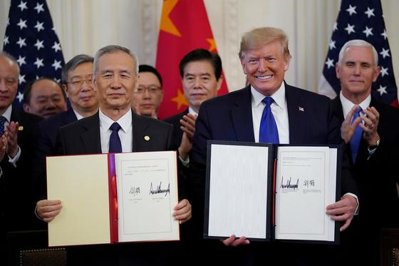 도널드 트럼프(오른쪽) 미 대통령과 류허 중국 부총리가 미중 무역 1단계 합의문을 들고 웃고 있다 . [로이터]