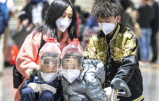 지난 1일(현지시간) 중국 광둥성 광저우 공항에서 플라스틱통을 잘라만든 얼굴 보호장비를 한 아이들이 가족과 함께 공항을 빠져나가고 있다. [EPA=연합뉴스]
