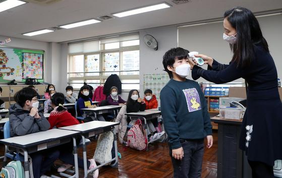 지난 3일 오전 개학한 부산 부산진구 양정초등학교에서 선생님이 신종 코로나바이러스 감염증 예방을 위해 어린이들의 체온을 측정하고 있다. 사진은 기사와 직접적인 관련이 없음. [연합뉴스]
