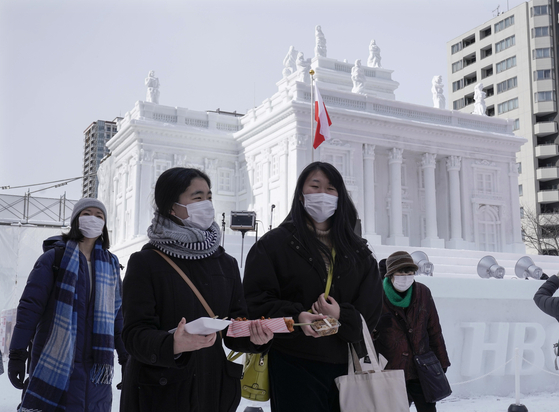 일본 홋카이도 삿포로시 오도리공원에서 눈축제가 한창인 가운데 4일 마스크를 쓴 관광객들이 조형물들을 관람하고 있다. [EPA=연합뉴스]