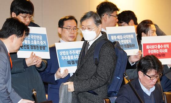 조흥식 국민연금기금위 부위원장이 5일 국민연금기금운용위원회에 참석, 마스크를 쓰고 회의실로 들어서고 있다. 뒤로 참여연대 관계자들이 피케팅을 하고 있다. [연합뉴스]
