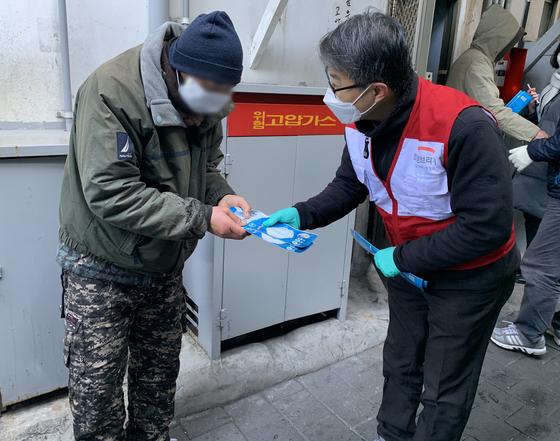 2월 5일 희망브리지 전국재해구호협회 배천직 구호팀장이 영등포 쪽방촌 주민에게 방역 마스크를 전달하고 있다.