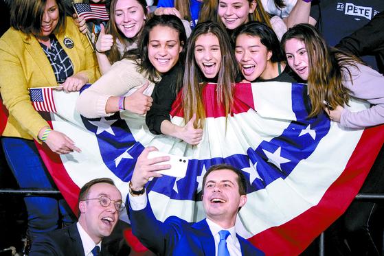 민주당 대선주자인 피트 부티지지 전 인디애나 사우스벤드 시장(오른쪽)과 배우자 채스턴 글래즈먼(왼쪽)이 3일 아이오와 코커스 현장에서 지지자들과 셀피를 찍고 있다. [EPA=연합뉴스]