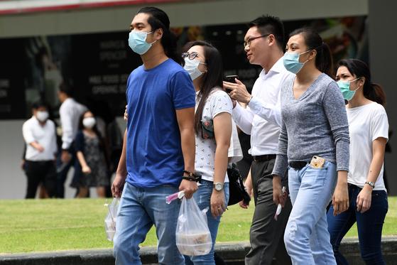 신종코로나 확진자가 급증하고 있는 싱가포르에서 직장인들이 마스크를 쓰고 걷고 있다. [AFP=연합뉴스]