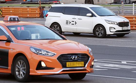 서울 도심에서 운행 중인 택시(아래)와 '타다' 차량. 정부는 택시운전자격 보유자들에 한해 타다 등 승차공유 차량을 운행할 수 있도록 제도를 개편할 계획이다. [뉴시스]