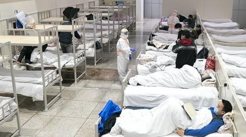 중국의 신종 코로나바이러스 감염자들이 지난 5일 컨벤션 센터를 개조한 우한의 임시 병원에 수용돼 있는 모습. [연합뉴스]