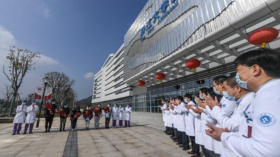 신종 코로나바이러스에 감염됐다가 중국 저장대 제1의원에서 치료를 받고 퇴원하는 사람들에게 의료진이 박수를 보내고 있다. [중국 신화망 캡처]