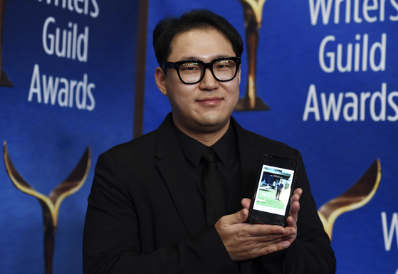 '기생충' 공동 각본가 한진원씨가 1일(현지시간) 각본상을 수상한 미국작가조합(WGA) 시상식에서 영화 포스터를 휴대폰에 띄워 보였다. [AP=연합뉴스]