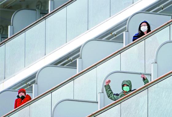 6일 일본 요코하마항에 정박 중인 크루즈선 다이아몬드 프린세스호 내 선실에 각기 격리된 승객들이 손을 흔들고 있다. 이들 승객은 바다를 조망 할 수 있는 비싼 선실에 묵고 있다. [EPA=연합뉴스]