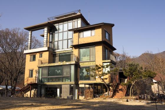 용인 '생각을담는집'. 1층은 북카페, 3~4층은 숙소로 사용한다. 큼지막한 창과 수많은 화초 덕에 온실처럼 아늑한 분위기다.