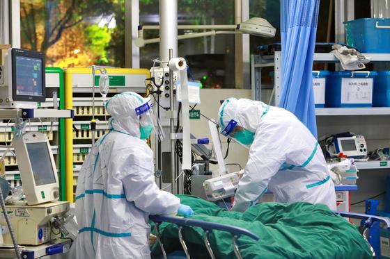 중국 후베이성 우한의 우한대학 부속 중난병원에서 보호복을 입은 의료진이 신종 코로나바이러스에 의한 폐렴 환자를 치료하고 있다. [로이터=연합뉴스]