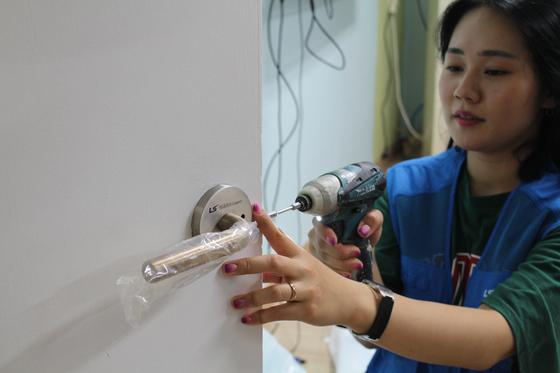 LS니꼬동제련 여직원이 지역아동센터에 구리 소재의 문손잡이를 설치하고 있다. [사진 LS니꼬동제련]