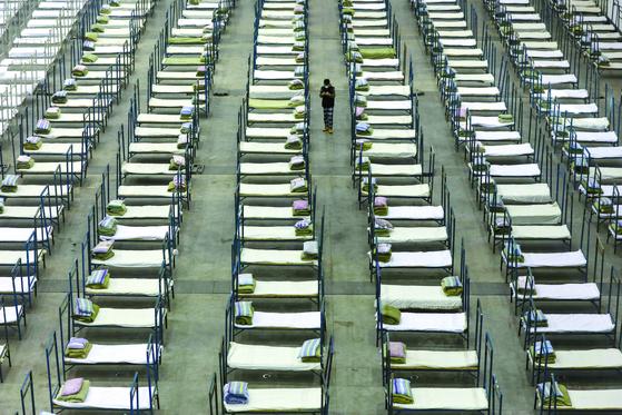 지난 4일 중국 후베이성 우한의 컨벤센센터에 마련된 임시 병상들 사이를 한 작업자가 걷고 있다. 신종 코로나바이러스 감염증의 진원지인 우한에선 확진자와 사망자가 계속 늘고 있다. [AP=연합뉴스]