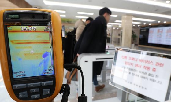 지난 7일 오후 충북대학교 도서관에서 학생들이 신종 코로나바이러스 예방을 위해 설치된 열화상 카메라 앞을 지나가고 있다. [뉴스1]