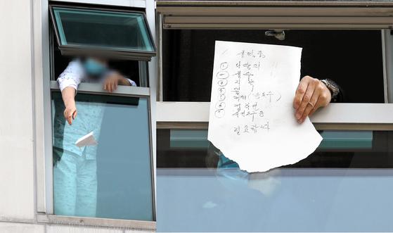 지난 6일 오후 광주 광산구 21세기병원에서 3층에 격리된 환자와 보호자가 필요한 생필품을 종이에 적어 창문 너머로 보이고 있다. 왼쪽은 한 환자가 요구사항이 적힌 쪽지를 창문 밖으로 던지는 모습. [연합뉴스]