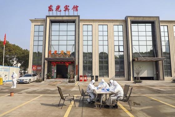 지난 3일 중국 후베이성 우한시가 격리포인트로 지정한 한 호텔 앞에 시 당국 관계자들이 앉아 있다. [AP=연합뉴스]