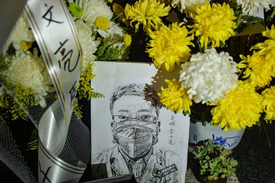 지난 7일 중국 우한중심병원에 마련된 의사 리원량의 임시 추모소에 그의 그림과 국화가 놓여 있다. [AFP=연합뉴스]