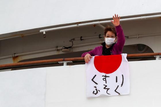 """7일 일본 요코하마에 정박 중인 크루즈선 의 한 승객이 '의약품 부족""""이라고 적힌 일본 국기를 발코니에 내건 뒤 손을 흔 드는 모습[로이터=연합뉴스]"""