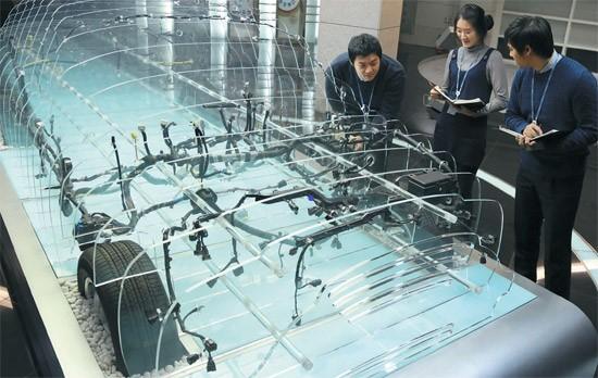 현대·기아차에 와이어링 하네스를 납품하는 경신의 직원이 시뮬레이션 룸에 설치한 제품을 살펴보고 있다.다. [사진 경신]