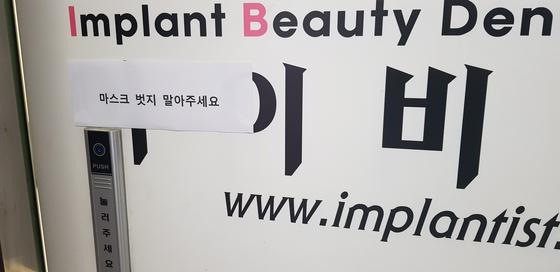 서울 중구의 아이비치과 입구에 '마스크 벗지 말아달라'는 안내문이 붙어 있다.