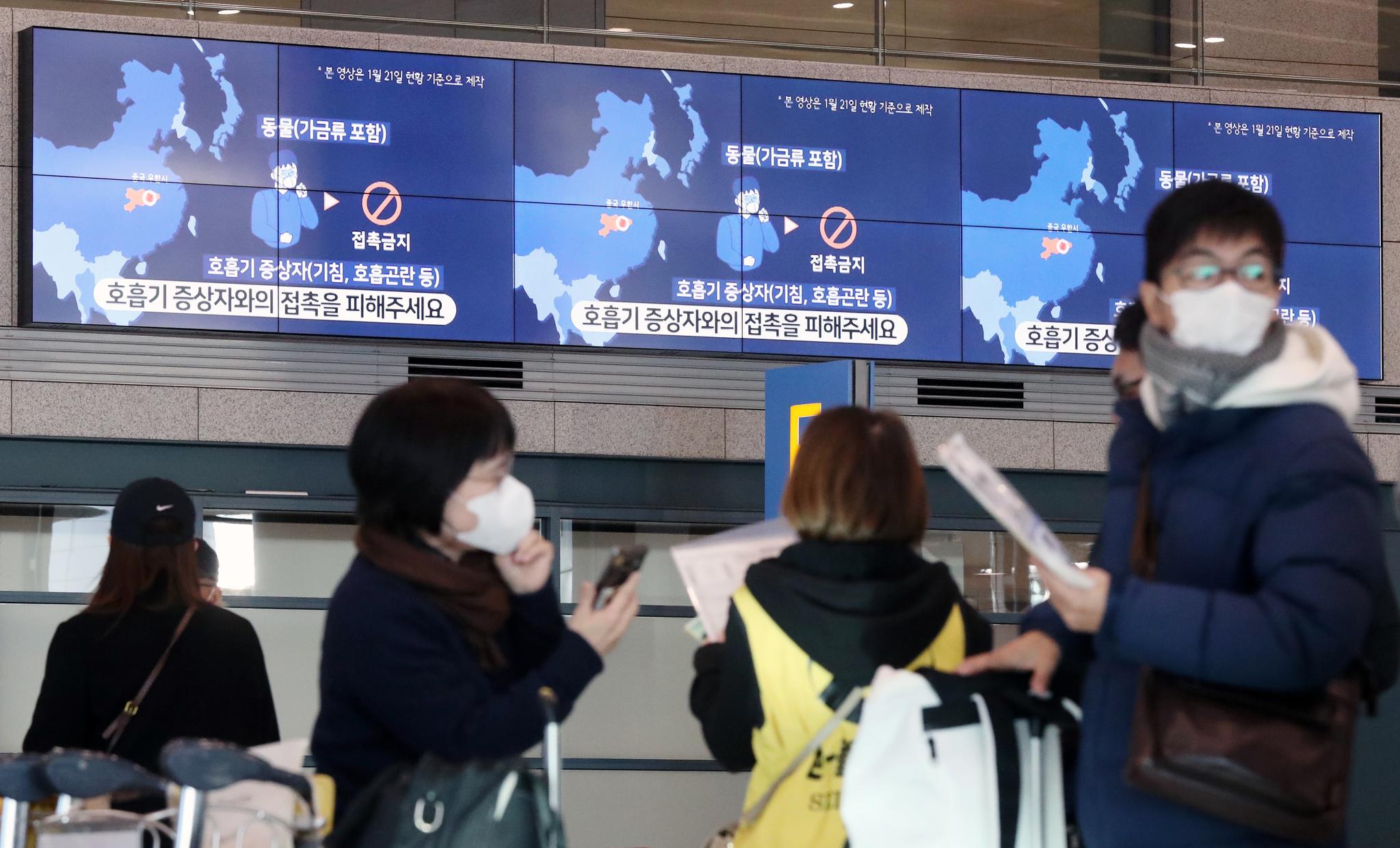 지난 5일 인천국제공항 제1여객터미널 입국장에서 마스크를 쓴 여행객 뒤로 신종 코로나 감염 주의 안내가 나오고 있다. [뉴스1]