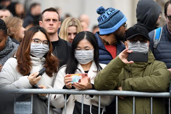 지난달 26일 영국 런던에서 마스크를 쓴 관광객들이 거리에서 펼쳐지는 중국 설맞이 행사를 관람하고 있다. [AFP=연합뉴스]