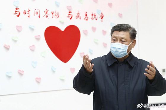 시진핑 중국 국가주석이 10일 오후 신종 코로나 사태 이후 처음으로 현장 방문에 나서 베이징의 병원과 주민센터 등을 찾았다. 시 주석 뒤의 하트 위로 '시간을 다퉈 역병과 싸우자'는 구호가 보인다. [중국 신화망 캡처]