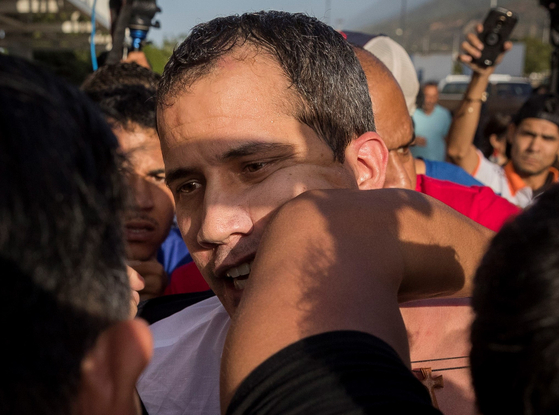 후안 과이도 국회의장이 11일(현지시간) 베네수엘라 시몬 볼리바르 국제공항에 도착해 반대파 지지자에게 팔꿈치로 공격을 받고 있다. [ EPA=연합뉴스]
