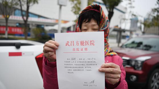 중국 우한의 팡창병원에서 치료를 받다 건강을 되찾은 환자가 퇴원해도 좋다는 허가증을 내보이고 있다. [중국 신화망 캡처]