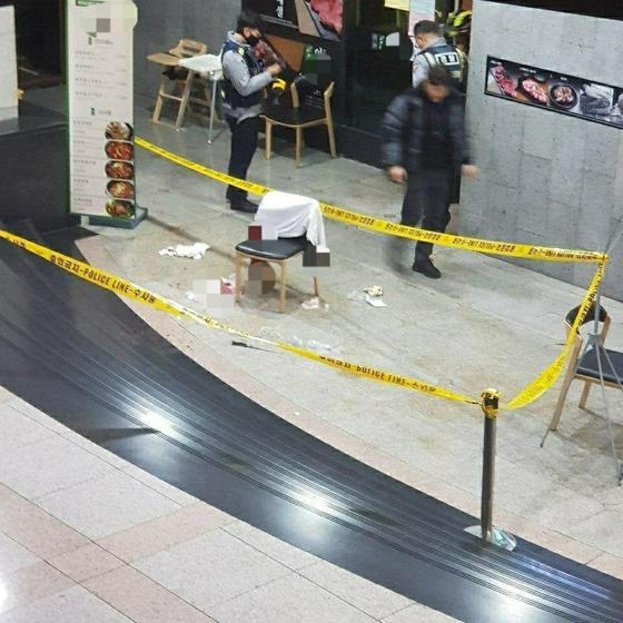 12일 칼부림 사건이 발생한 서울 여의도의 한 증권사 지하 고깃집 앞에 폴리스 라인이 설치돼 있다. 피해자가 쓰러져 있었던 것으로 추정되는 곳에 피묻은 천과 의자가 놓여져 있다. [독자 제공]