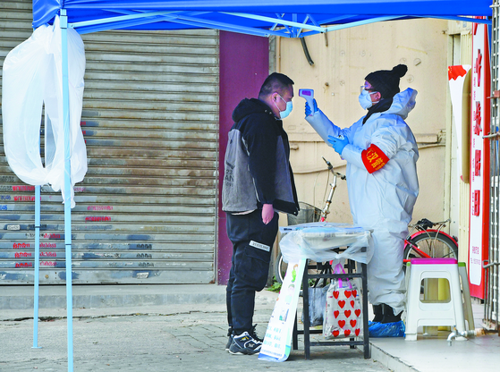 중국 우한의 한 주택가에서 지역 보건센터 직원이 10일(현지시간) 마을 방문객의 체온을 측정하고 있다. [신화=연합뉴스]