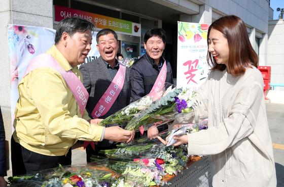 지난 11일 태안군청 민원실 앞에서 가세로 태안군수(왼쪽)가 화훼협회 태안분회 농가들과 함께 군민에게 꽃을 나눠주고 있다. [사진 태안군]
